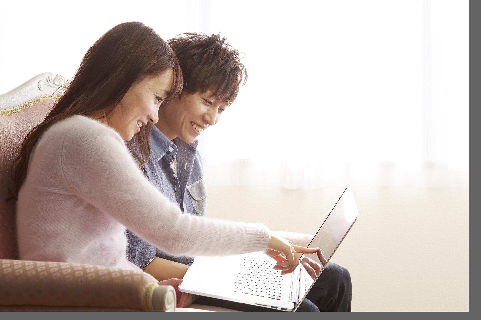 ノートパソコンを見るカップル